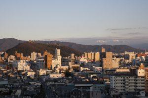 夕日に照らされて美しい松山城の遠景。遠くに石鎚山が見える。