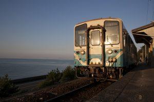 伊予灘の海と夕日に照らされた列車。