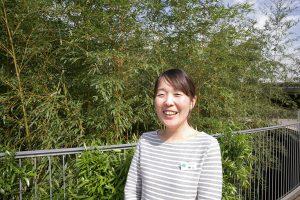 笑顔の広報スタッフ楠山さん。植物に囲まれると笑顔が増える!?